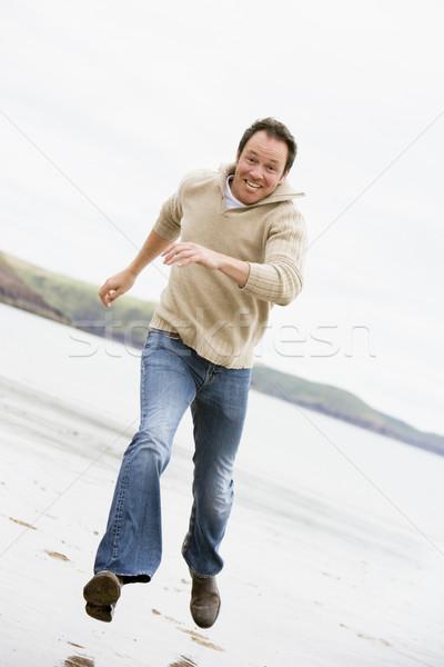 Man running on beach smiling Stock photo © monkey_business