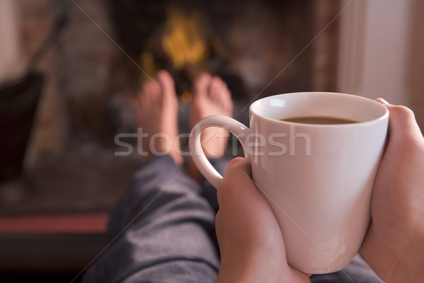 Stock photo: Feet warming at fireplace with hands holding coffee