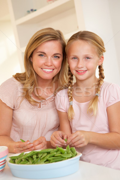 Young woman with child splitting pea in kitchen Stock photo © monkey_business