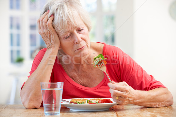 Sick older woman trying to eat Stock photo © monkey_business