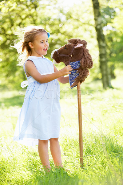Young Girl Playing With Hobby Horse In Summer Field Stock photo © monkey_business
