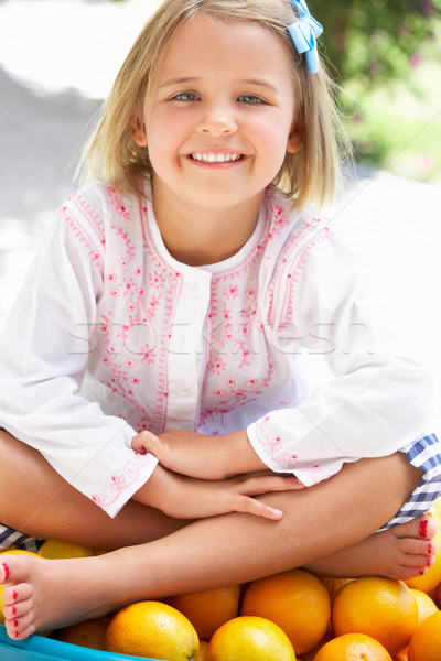 Girl Sitting In Wheelbarrow Filled With Oranges Stock photo © monkey_business