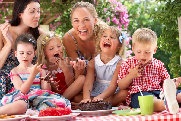 Children And Mothers Eating Jelly And Cake At Outdoor Tea Party Stock photo © monkey_business