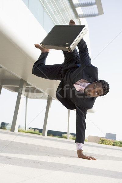 Businessman outdoors by building standing on one hand Stock photo © monkey_business