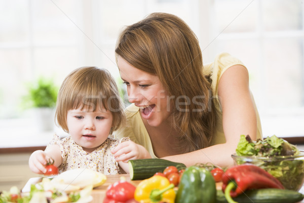 Stock photo: Mother and daughter in kitchen making a salad smiling
