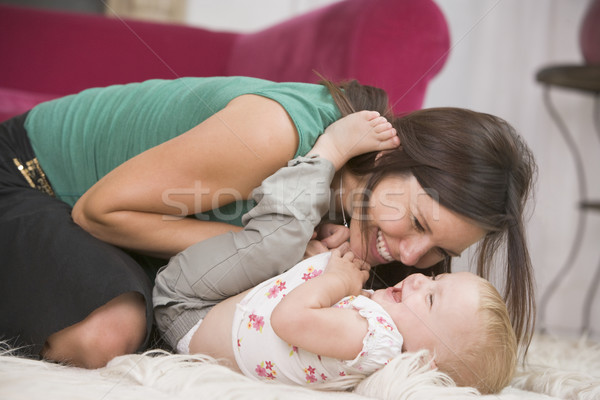 Mother in living room playing with baby smiling Stock photo © monkey_business
