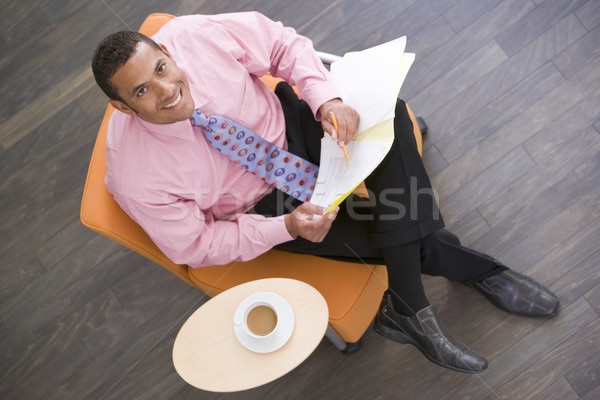 Businessman sitting indoors with coffee and folder smiling Stock photo © monkey_business