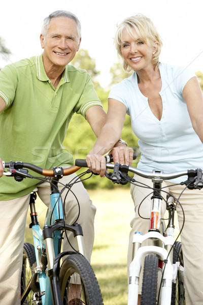 Stock photo: Mature couple riding bikes