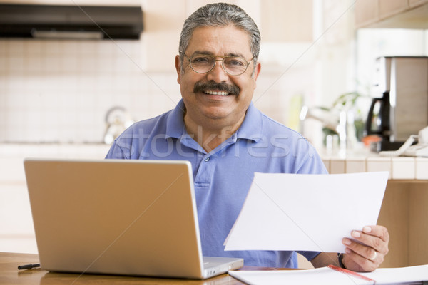 Man in kitchen with laptop and paperwork smiling Stock photo © monkey_business