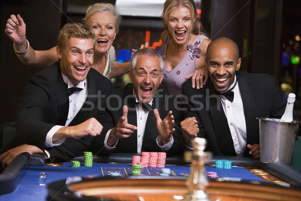 Group of friends celebrating at roulette table Stock photo © monkey_business