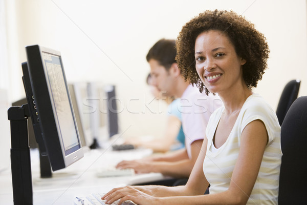 Three people in computer room typing and smiling Stock photo © monkey_business