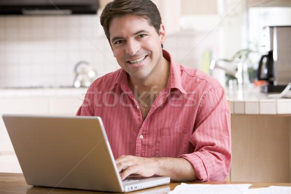 Foto stock: Hombre · cocina · usando · la · computadora · portátil · sonriendo · ordenador · feliz