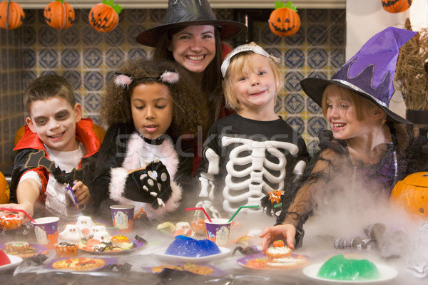 Four young friends and a woman at Halloween eating treats and sm Stock photo © monkey_business