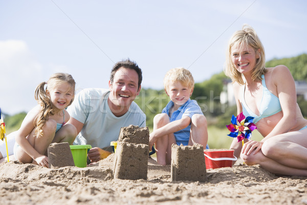 Family on beach making sand castles smiling Stock photo © monkey_business
