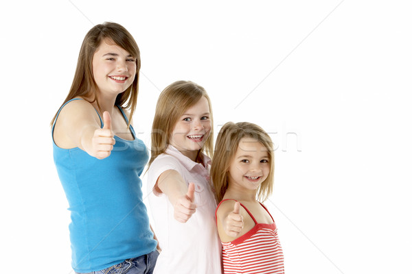 Three Girls Giving Thumbs Up Gesture In Studio Stock photo © monkey_business