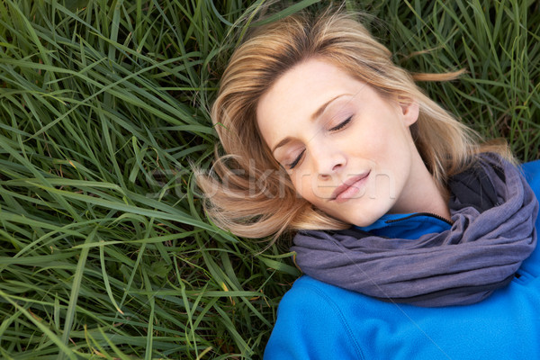 Young woman napping alone on grass Stock photo © monkey_business