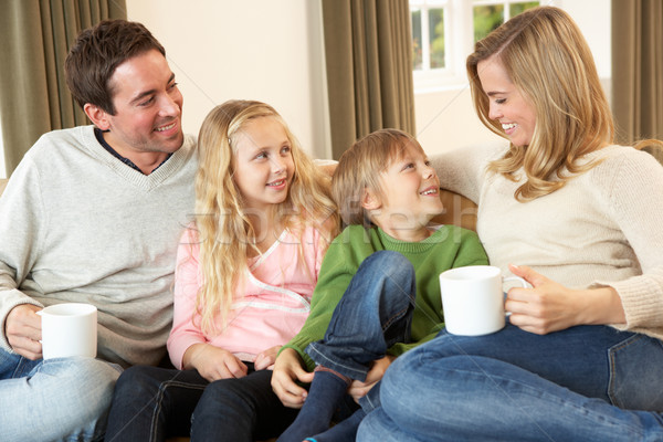 Happy young family sitting and talking on sofa Stock photo © monkey_business