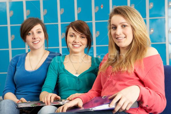 Female Teenage Students Relaxing By Lockers In School Stock photo © monkey_business