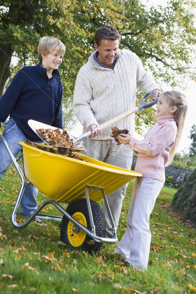 Children helping father to collect autumn leaves Stock photo © monkey_business