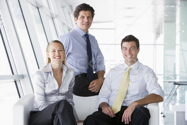 Three businesspeople sitting in office lobby smiling Stock photo © monkey_business