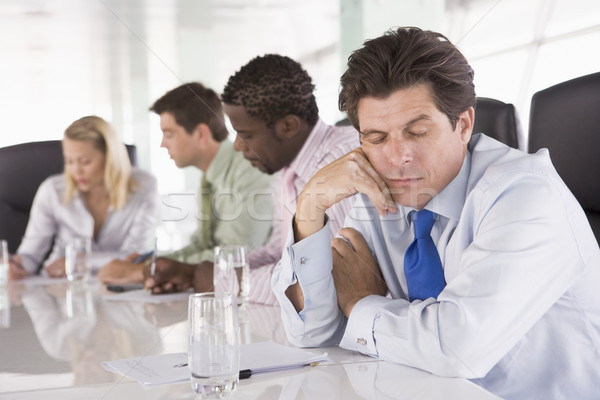 Four businesspeople in boardroom with one businessman sleeping Stock photo © monkey_business