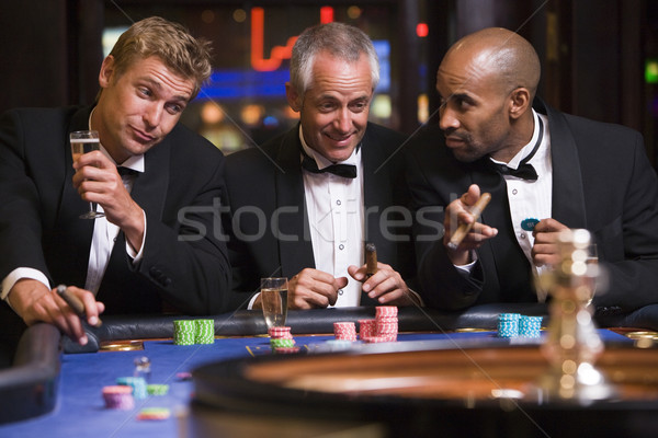 Three men gambling at roulette table Stock photo © monkey_business