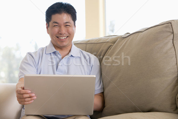 Hombre salón usando la computadora portátil sonriendo ordenador casa Foto stock © monkey_business