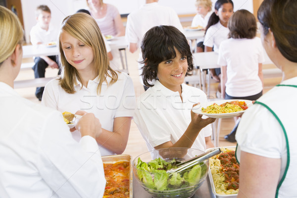 Lunchladies serving plates of lunch in school cafeteria Stock photo © monkey_business