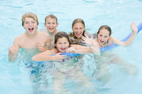 Five young friends in swimming pool playing and smiling Stock photo © monkey_business