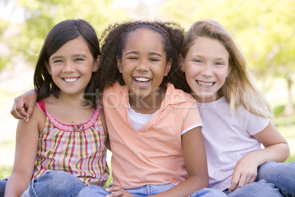 Stock photo: Three young girl friends sitting outdoors smiling