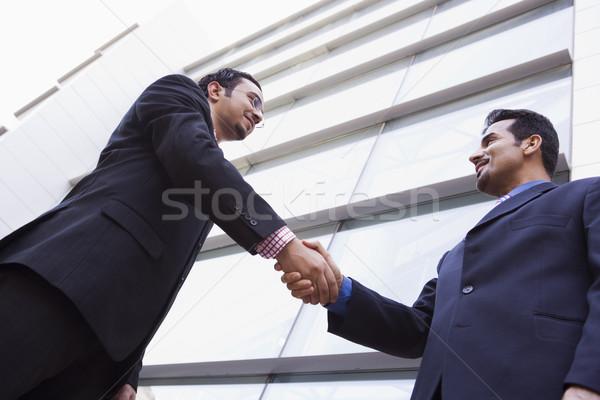 Foto stock: Dos · empresarios · apretón · de · manos · fuera · edificio · de · oficinas · moderna