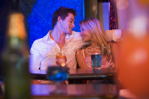 Happy young couple sitting in a nightclub, smiling at each other Stock photo © monkey_business
