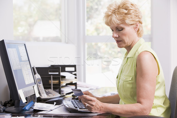 Woman in home office at computer with credit card frowning Stock photo © monkey_business