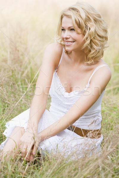 Сток-фото: женщину · сидят · улице · улыбающаяся · женщина · улыбаясь · трава