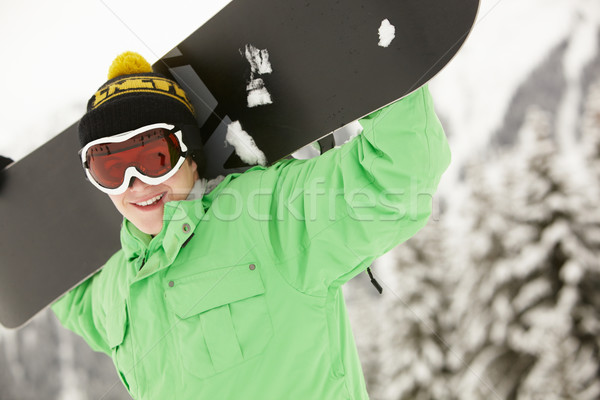 Teenage Boy With Snowboard On Ski Holiday In Mountains Stock photo © monkey_business