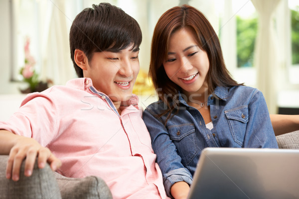 Stock photo: Young Chinese Couple Using Laptop Whilst Relaxing On Sofa At Hom