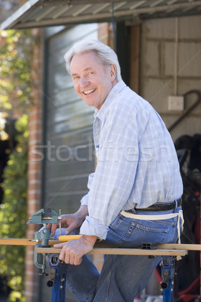 Stock photo: Man at shed sitting on tool bench smiling