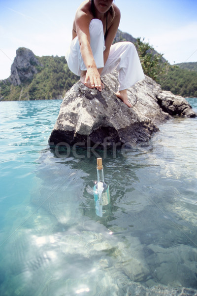 Young woman reaching for a message in a bottle Stock photo © monkey_business