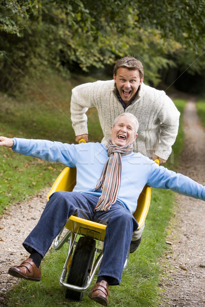 Grown up son pushing father in wheelbarrow Stock photo © monkey_business