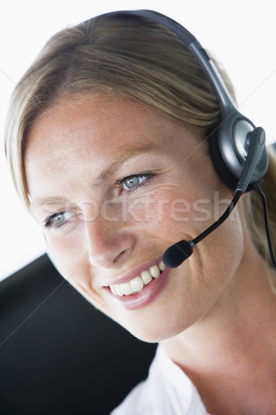 Businesswoman in office wearing headset and smiling Stock photo © monkey_business