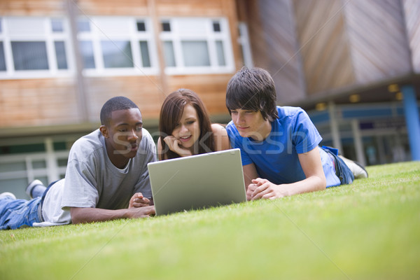 College students using laptop on campus lawn Stock photo © monkey_business