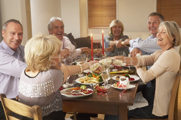 Stock photo: Friends Pulling Christmas Crackers At A Dinner Party