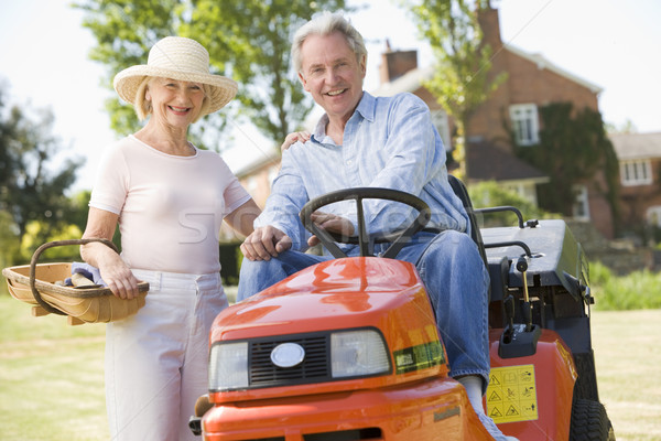 Couple outdoors with tools and lawnmower smiling Stock photo © monkey_business