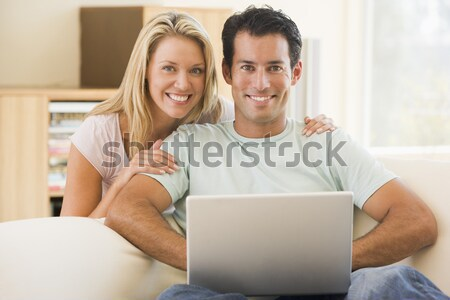 Stock photo: Couple in living room using laptop smiling