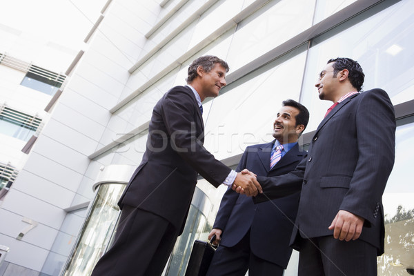 Stock photo: Group of businessmen shaking hands outside office