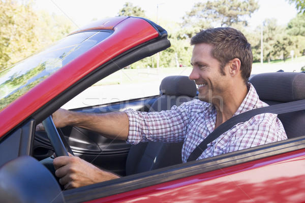 Man driving convertible car smiling Stock photo © monkey_business