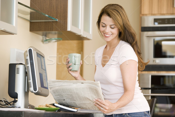 Woman in kitchen at computer with newspaper and coffee smiling Stock photo © monkey_business