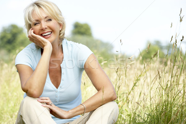 Portrait of mature woman sitting in countryside Stock photo © monkey_business
