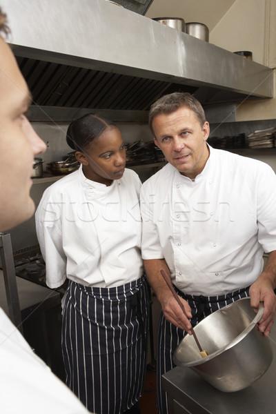 Chef Instructing Trainees In Restaurant Kitchen Stock photo © monkey_business