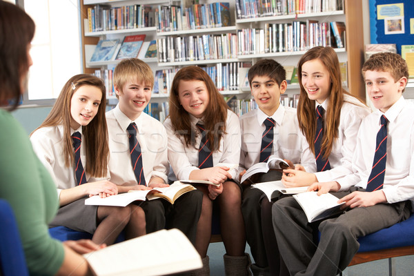 Teenage Students In Library Reading Books With Tutor Stock photo © monkey_business